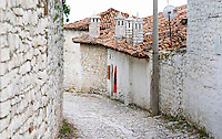 Narrow cobble stone street with traditional ottoman white stone houses. An Albanian flag on the wall. Four stone chimneys. Berat upper citadel old walled city. Albania, Balkan, Europe.