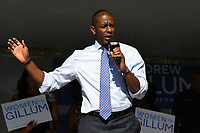 """FORT LAUDERDALE FL - OCTOBER 29: A man carrying a """"God Bless The NRA"""" sign is escorted out of the rally after getting into an argument with campaign supporters as Former Attorney General of the United States Eric Holder campaigns with Democratic Florida gubernatorial nominee Andrew Gillum during a grassroots campaign event held at the African American Research Library on October 29, 2018 in Fort Lauderdale, Florida. Credit: mpi04/MediaPunch"""