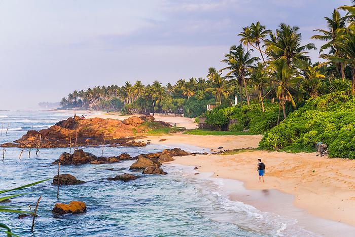 Tourist walking along Midigama Beach, near Weligama on the South Coast of Sri Lanka, Asia. This is a photo of a tourist walking along Midigama Beach, near Weligama on the South Coast of Sri Lanka, Asia.