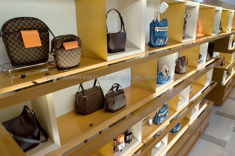 "10/9/2005--Paris, France.Handbags on sale on the ground floor of French luxury goods maker Louis Vuitton who opened its biggest store yet on the Champs Elysees in Paris, after a 20-month redesign and enlargement project. The flagship store at 101, avenue des Champs Elysees has been redecorated and enlarged at an undisclosed cost. ..About 300 VIPs, including Hollywood stars Sharon Stone and Uma Thurman and French actress Catherine Deneuve, attended the official opening before American designer Marc Jacobs unveils his ready-to-wear spring-summer 2006 collection for Louis Vuitton. Behind the face-lift are US architects Eric Carlson and Peter Marino who sought to create a feeling of the famous promenade along the Champs Elysees continuing into the store...Throughout, it has features alluding to aspects of the fabled Champs Elysees such as brown and beige limestone flooring which echoes the paving stones on the street outside. Features include a light sculpture by American James Turrell, a 20-metre (65 feet) long ""travelling staircase"" showcasing the work of American video artist Tim White-Sobieski and an elevator linking the store to the top floor by Denmark's Olafur Eliasson..Photograph By Stuart Isett.All photographs ©2005 Stuart Isett.All rights reserved."