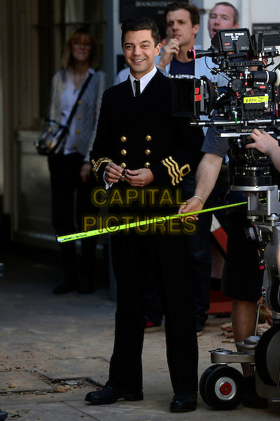 Dominic Cooper<br /> Filming on the set of 'Fleming' where Dominic Cooper stars as Ian Fleming, Central London, England.<br /> 29th June 2013<br /> tv mini series full length black suit uniform camera cast crew measuring tape <br /> CAP/IA<br /> &copy;Ian Allis/Capital Pictures