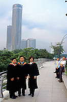 Singapore. Downtown. Town center. A group of university graduate students (two men and a woman) on Esplanade bridge. The giant high-rise building is part of the Raffles City complex.  © 2001 Didier Ruef