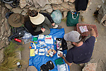 Andean Mountain Cat (Leopardus jacobita) veterinarian, Deana Clifford, and biologist, Juan Reppucci, checking medical supplies for collaring, Abra Granada, Andes, northwestern Argentina