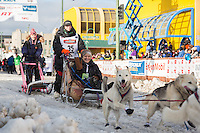 Ellen Halverson and team leave the ceremonial start line with an Iditarider at 4th Avenue and D street in downtown Anchorage, Alaska during the 2015 Iditarod race. Photo by Jim Kohl/IditarodPhotos.com