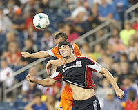 Houston Dynamo forward Cam Weaver (15) and New England Revolution defender Stephen McCarthy (15) battle for head ball.  In a Major League Soccer (MLS) match, Houston Dynamo (orange) defeated the New England Revolution (blue), 2-1, at Gillette Stadium on July 13, 2013.