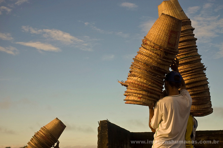 Worker carries açaí baskets at Macapa city harbor, Brazil.
