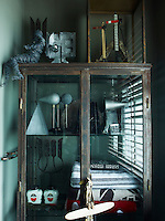 A glass-fronted cabinet in the guest bathroom displays a collection of random objects as well as a few towels