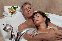 A baby-boomer couple enjoys a bath in a spa. *Model and property release available*