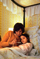 A concerned mother looks at an oral thermometer with her ill daughter in bed.