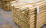 Wooden fence posts piled up in a builder's merchant yard, UK