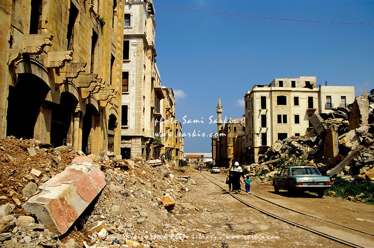 People walking past buildings destroyed by the Lebanese Civil War, Beirut, Lebanon.
