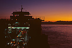 Ferry boat with cars loading onto passenger ferry boat at sunset with Puget Sound and Olympic Mountains Seattle Washington State USA..