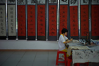 A girl student practises Chinese calligraphy at Luocun Experimental Primary School in Nanhai district of Foshan city, Guangdong province, November 9, 2011.
