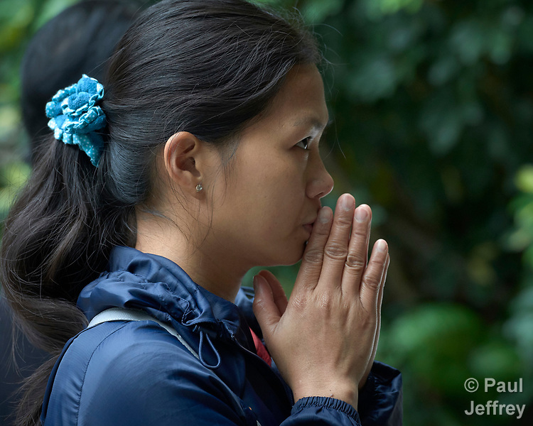 A migrant domestic worker from the Philippines prays by an outdoor altar at St Joseph's Catholic Church in Hong Kong. Some 370,000 foreign domestic workers live in Hong Kong, about five percent of the population. Most are women from the Philippines and Indonesia.