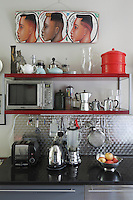 A variety of shiny kitchen appliances is collected on the granite work top of a kitchen unit