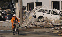 A rescue worker carries a child on a bike in front of devastation caused by the Japanese earthquake in Sendai, Japan. One of the biggest earthquakes ever recorded struck off the coast of Japan on 11 Mar 2011 had killed thousands of people. The death toll was expected to rise dramatically, with tens of thousands reported missing.<br /> 13 Mar 2011
