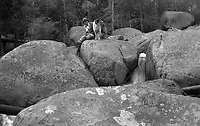 A woman and a dog setaed on a boulder in a stream in Western United States, circa 1930's.   (photo: www.bcpix.com)