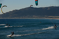 Spain, Andalusia, Tarifa, kite surfer at beach of atlantic ocean, behind wind farm on mountains