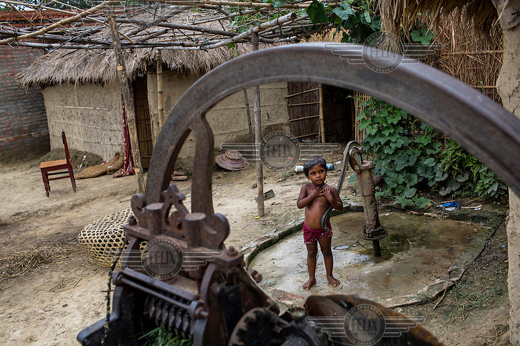 A young girl bathes at a stand pipe in Ramgarwa village.