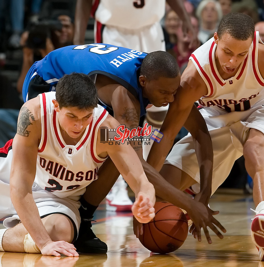 Stephen Rossiter (23) and Stephen Curry (30) of the Davidson Wildcats battle with Nolan Smith (2) of the Duke Blue Devils for a loose ball during second half action at Bobcats Arena December 1, 2007 in Charlotte, NC.  The Blue Devils defeated the Wildcats by the score of 79-73.