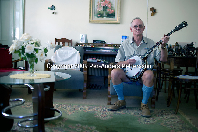 PHILIPPOLIS, SOUTH AFRICA FEBRUARY 24: Jaani Cilliers, age 65, plays on his banjo in his living room on February 24, 2009 in Philippolis, in the free state province, South Africa. Mr. Cilliers, an Afrikaner, used to be a sheep farmer but he is now retired and lives with his wife in the village. The small village is one of the oldest Afrikaner villages in South Africa and was a thoroughfare for the old road between Johannesburg and Cape Town.  Most people make a living on farming sheep, as the climate is too harsh for other forms of farming. Most of the people are white and conservative in this area, about 400 miles south of Johannesburg. (Photo by: Per-Anders Pettersson/Getty Images).