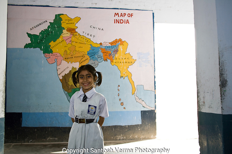 A young girl child in her school uniform standing against the map of India, smiling into the camera. Photograph © Santosh Verma