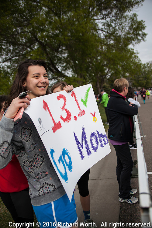 Young fans along the finish line at the Colfax Marathon hold up a sign cheering for their mom, a half marathon runner.