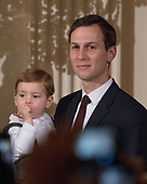 Jared Kushner holds his son Theodore as United States President Donald J. Trump makes remarks as the President and first lady Melania Trump host a Chanukah reception in the East Room of the White House in Washington, DC on Thursday, December 7, 2017.<br /> Credit: Ron Sachs / CNP