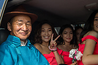 Mongolia, Ulaanbaatar. Sukhbaatar Square, family in wedding party in car.