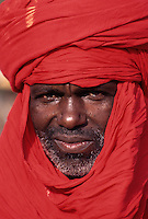 Akadaney, Niger.  Fulani Man, wearing a red Tuareg Tagelmust.  This is an example of how one culture, the Fulani, in close contact with another, may adopt the other's clothing styles.