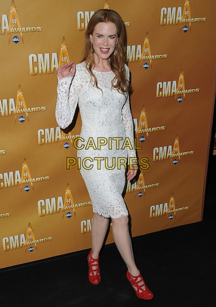 NICOLE KIDMAN  .44th Annual CMA Awards, Country Music's Biggest Night, held at Bridgestone Arena, Nashville, Tennessee, USA, 10th November 2010.CMAs country music full length white lace long sleeve dress red shoes cut out suede peep toe hand waving.CAP/ADM/GS.©George Shepherd/AdMedia/Capital Pictures.