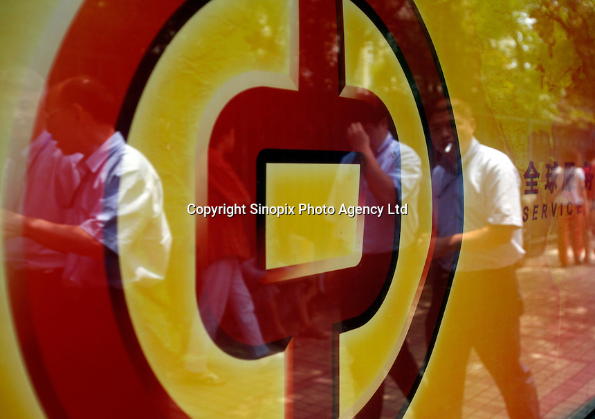An image of office workers on the street is reflected from an advertisement displaying a Bank of China logo in Shanghai, China..