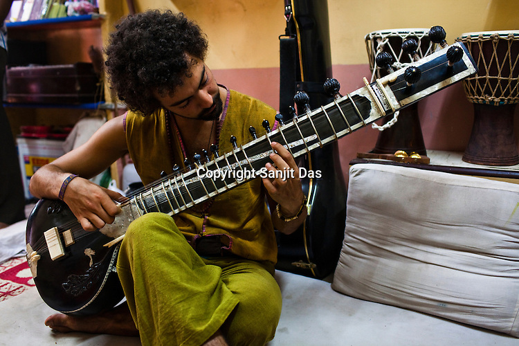A young German student, Igor plays the sitar during the music lesson in a small shop in the ancient city of Varanasi in Uttar Pradesh, India. Photograph: Sanjit Das/Panos