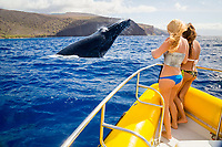 Two girls (MR) on a whale watching boat out of Lahaina, Maui, get a close up look at a breaching humpback whale, Megaptera novaeangliae, off the island of Lanai, Hawaii, digital composite