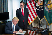 US President Donald J. Trump (L), with Secretary of Treasury Steven Mnuchin (R), participates in a financial services Executive Order signing ceremony in the US Treasury Department building in Washington, DC, USA, 21 April 2017. President Trump is making his first visit to the Treasury Department for a memorandum signing ceremony with Secretary Mnuchin.<br /> Credit: Shawn Thew / Pool via CNP