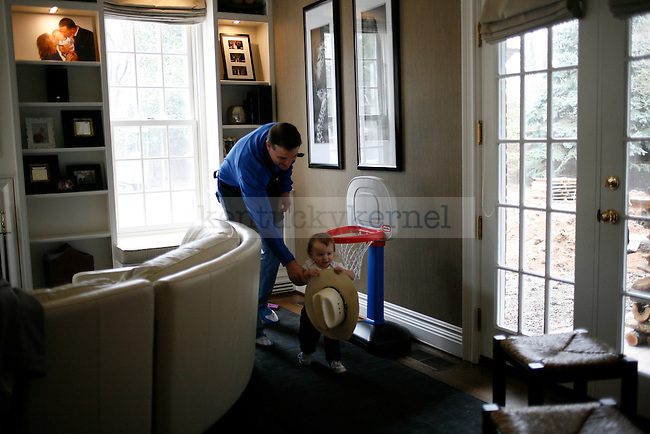 Matthew Mitchell chases his daughter, Saylor, around his living room at the taping of Coach's Kitchen in Lexington, Ky., on Wednesday, February 27, 2013. Saylor had just stolen his cowboy hat and was running because she didn't want to give it back. Photo by Tessa Lighty | Staff