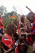Lolgorian, Kenya. Siria Maasai Manyatta; laibon elder offering cooked meat of sacrificed meat to moran.