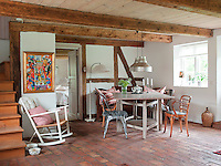 A brightly coloured painting stands out against the pale colours of the dining area