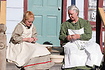 A grandmother figure and young girl snapping beans on their farmhouse porch in the country