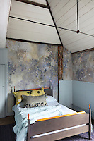 An attic bedroom with blue part-panelling and walls finished with a distressed finish paint effect. An original wall beam is exposed beside a single bed.