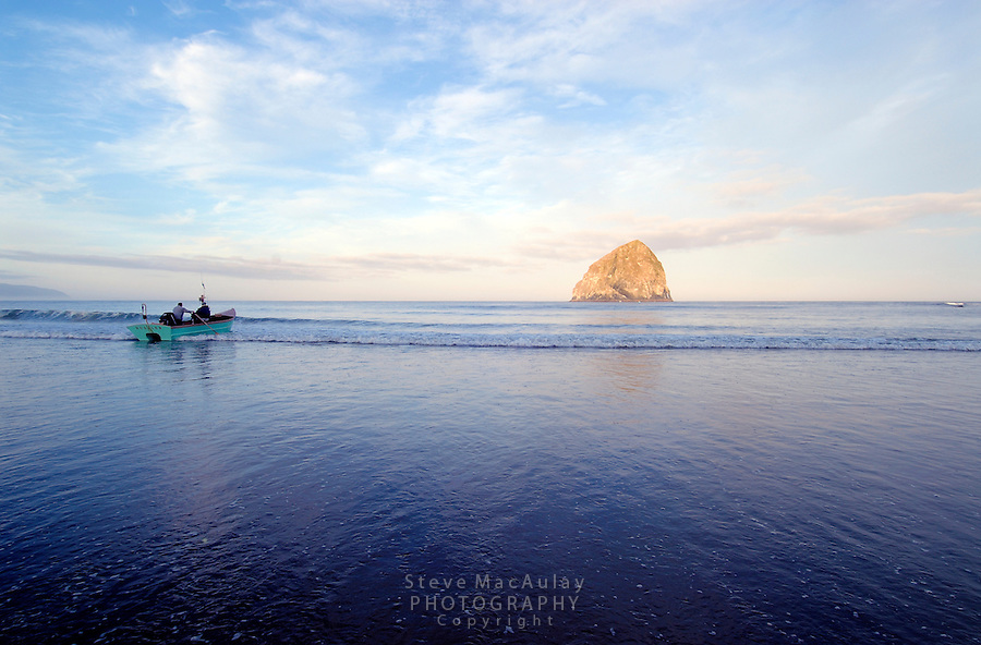 Launching a fishing dory through the surf at sunrise, Pacific City, Oregon.  Haystack Rock visible off-shore..