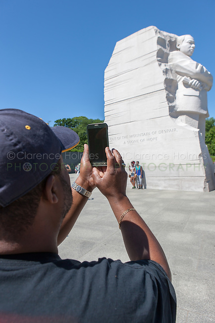 A man uses a smartphone to snap a photo of the Martin Luther King Memorial in Washington, DC.