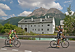 Bike riders wave as they pass through the small Swiss town of Punt-Chamues in the Graubunden region headed towards St. Mortiz, Switzerland