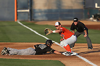 Josh Estill (38) of the Cal State Fullerton Titans takes a throw at first base as John Schuknecht (48) of the Cal Poly Mustangs dives back to the bag during a game at Goodwin Field on April 2, 2015 in Fullerton, California. Cal Poly defeated Cal State Fullerton, 5-0. (Larry Goren/Four Seam Images)