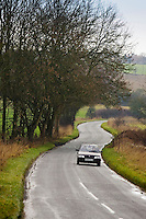 Car driving on a country road near Burford in the Cotswolds, Oxfordshire, United Kingdom