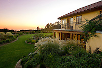 The outside of a private residence overlooking the Pacific Ocean in the distance.