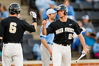 Charlie Morgan (24) of the Wake Forest Demon Deacons fist bumps with teammate Brett Armour (6) after scoring a run against the North Carolina Tar Heels at Wake Forest Baseball Park on March 9, 2013 in Winston-Salem, North Carolina.  The Tar Heels defeated the Demon Deacons 20-6.  (Brian Westerholt/Four Seam Images)