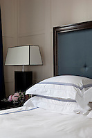 Detail of the bed with blue and white bed linen and blue leather headboard