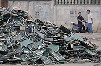 Villagers look at a pile of circuit boards and other discarded electronics in Guiyu in southern China's Guangdong province.  Each year, between 20 and 50 million tons of electronic waste is generated globally. Most of it winds up in the developing world. Some of the most popular destinations for dumping computer hardware include China, India, and Nigeria. It can be 10 times cheaper to ship waste to China than to dispose of it properly at home. With the market for e-waste expected to top $11 billion by 2009, it's lucrative to dump on the developing world.