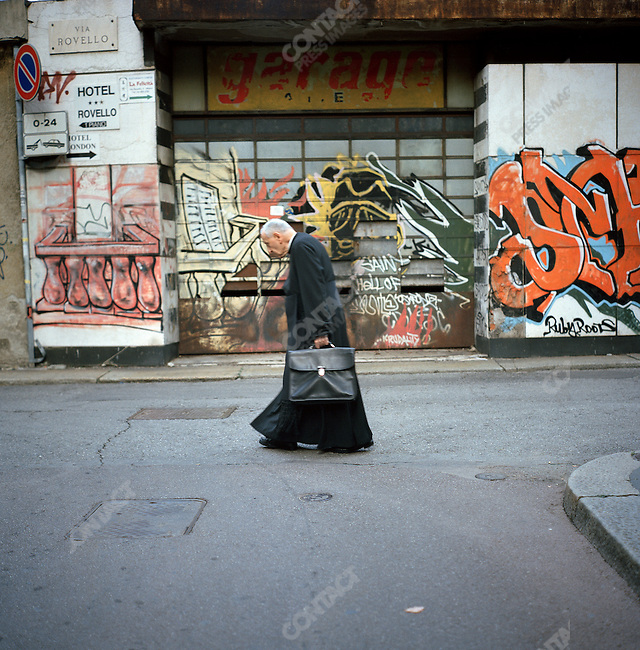 A priest passed a disused and graffitied garage in the centre of Milan. October 3, 2007